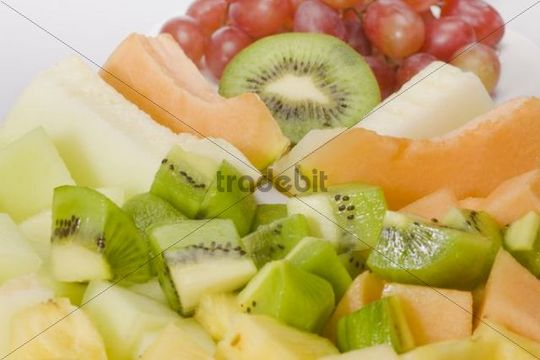 Sliced exotic fruit, sugar melon, honeydew melon, pineapple, kiwi and grapes