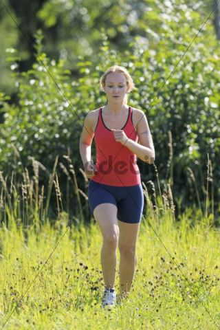 Young woman jogging through an unmown meadow