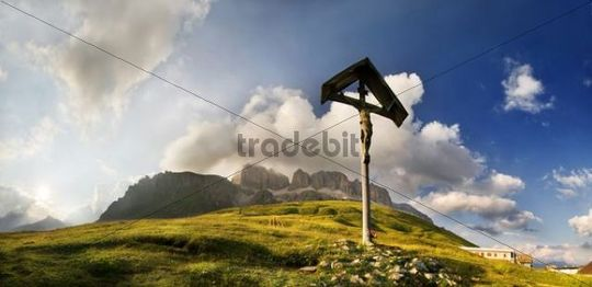 Cross at the Passo Pordoi with view of bizarre cloud formations and the Sella massif at sunset, province of Bolzano-Bozen, Italy, Europe