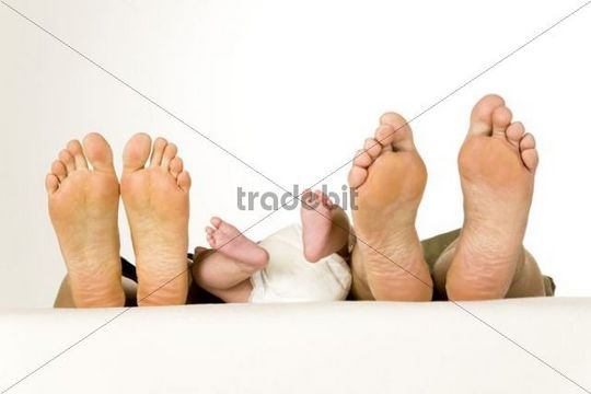 Feet of the father, mother and a baby