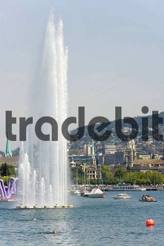 the Zurich Lake in Zurich, Switzerland. In the background the Grossmuenster Cathedral. In the foreground a fountain.