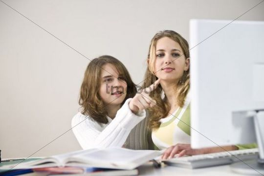 Two teenage girls working at a computer