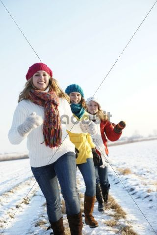 Teenage girls running in a snow covered landscape