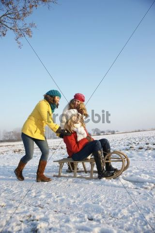Teenage girls in a snow-covered landscape, sitting on a sledge
