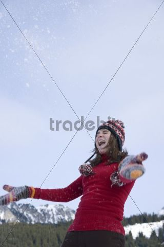 Teenage girl throwing snow into the air, laughing