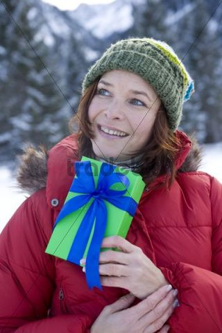 Woman holding a present in the snow in front of a winter landscape, smiling