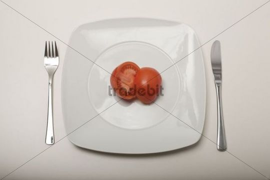 Tomato cut in half on a white plate