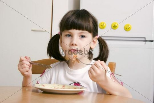 Eating little girl, 6 years old, with knife and fork