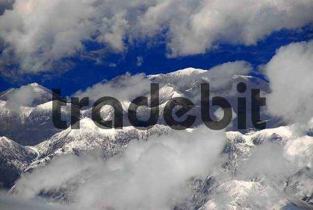 View from above on snow covered mountain ranges surrounded by clouds Tibet China