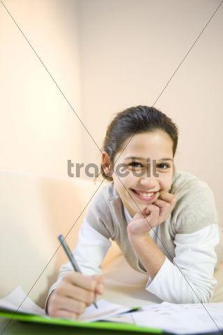 Girl doing homework on the sofa