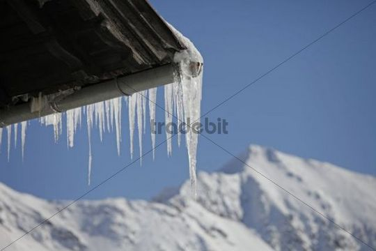 Icicles from the roof gutter of a house, in the back snow-covered mountains, Salzburg, Austria, Europe