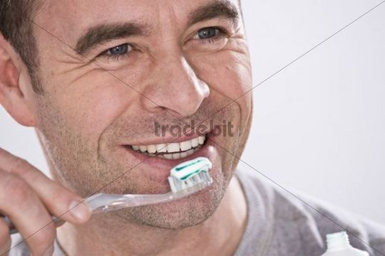 Smiling man holding a toothbrush