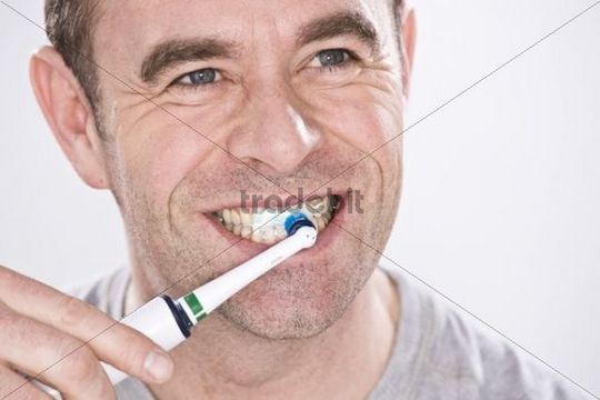 Man cleaning his teeth with an electric toothbrush