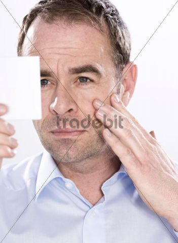 Man looking into a mirror to examine his wrinkles