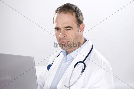 Smiling man wearing medical scrubs, with a stethoscope, looking at the computer