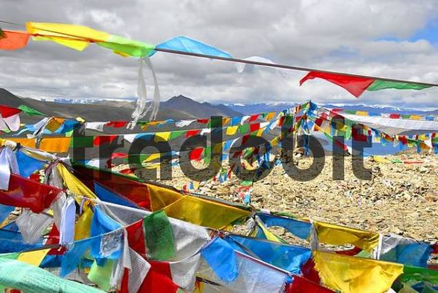Colourful prayer flags wave in the wind at Kamba-La Pass with view of lake Yamdrok-Tso Tibet China