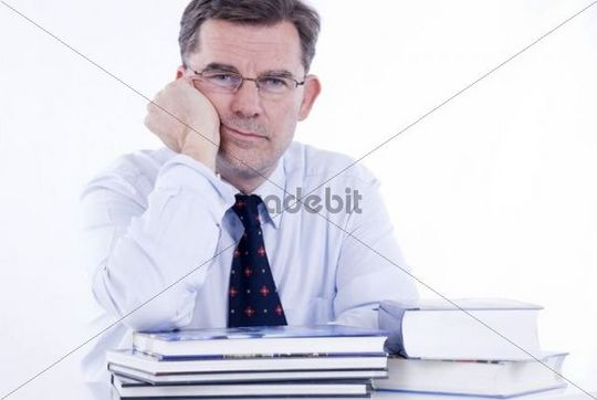 Man, 50, leaning on a stack of books