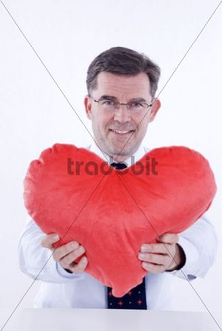 Attractive man, 50, holding a plush heart