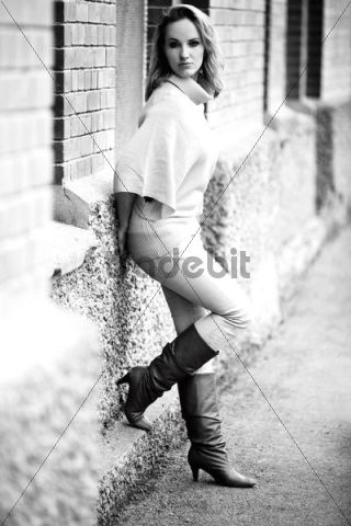 Woman leaning against a wall, wearing boots, tight trousers and a loose jumper