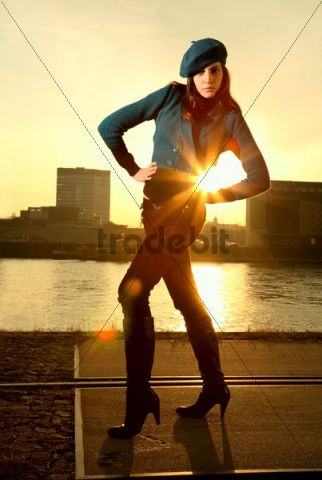 Woman standing on a road at the harbour, hands on her hips, blazing light from the low evening sun in the back
