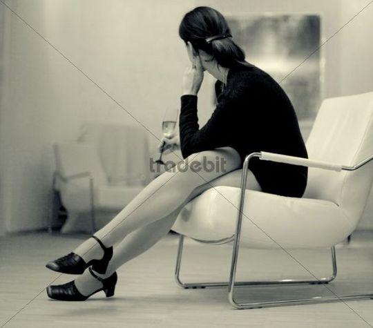 Frau sitzt in einem Lounge-Sessel und hält ein Glas Sekt in der Hand, ihre Beine sind übereinandergeschlagen