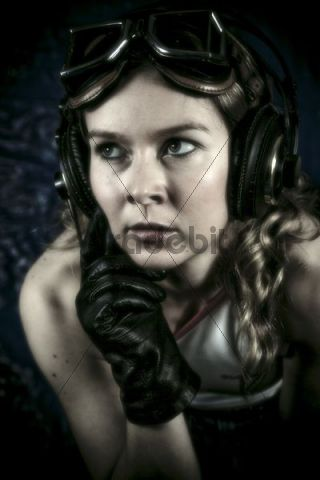 Young woman with headphones, motorcycle goggles and gloves