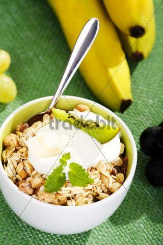 Muesli, quark, kiwi, grapes and bananas in a bowl