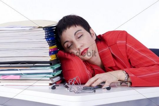 Exhausted businesswoman sleeping next to a pile of files in the office