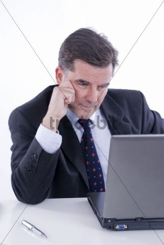 Businessman, over 50, working on a laptop