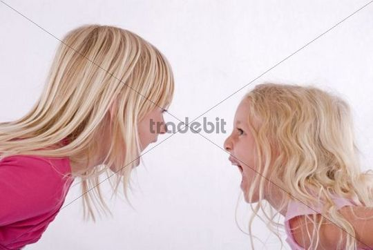 Two blonde girls screaming at each other