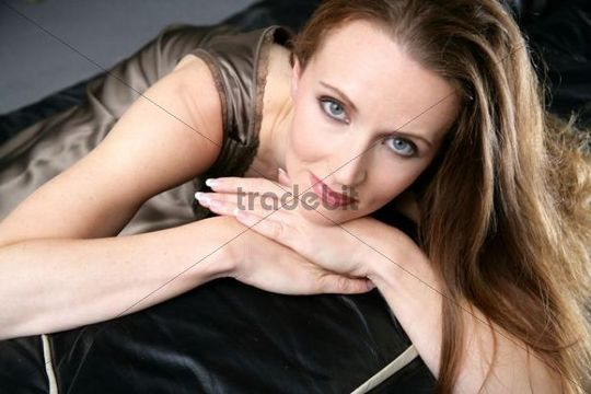 Long-haired woman leaning on a leather sofa