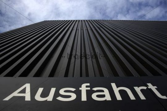 Ausfahrt sign, German for exit, on the facade of a car park, looking up to the sky