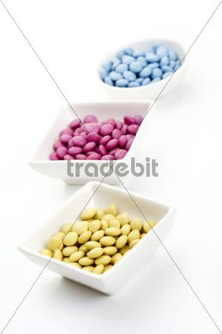 Coloured chocolate drops in white bowls