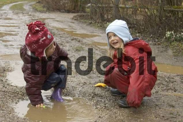 Children are playing during bad weather and rain in puddle and mud sludge