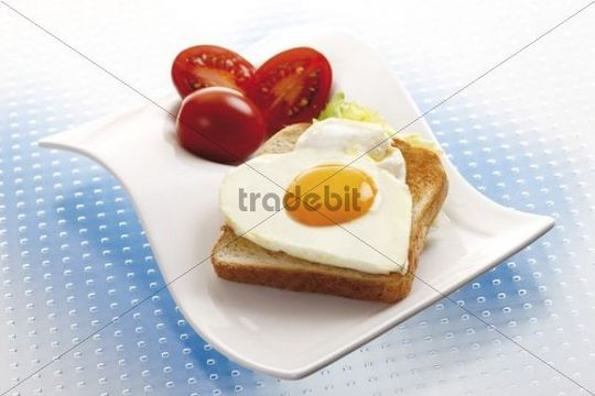 Toast with heart-shaped fried egg and tomatoes