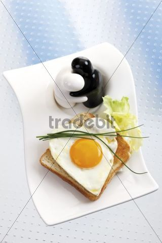 Toast with heart-shaped fried egg with chives and figures as salt and pepper shakers