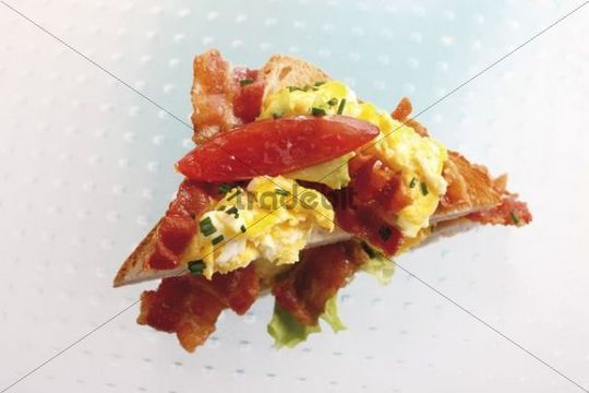 Toast sandwich with scrambled egg, bacon, chives and tomato