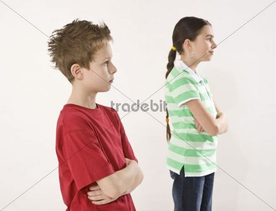 Boy and girl with arms crossed standing behind each other