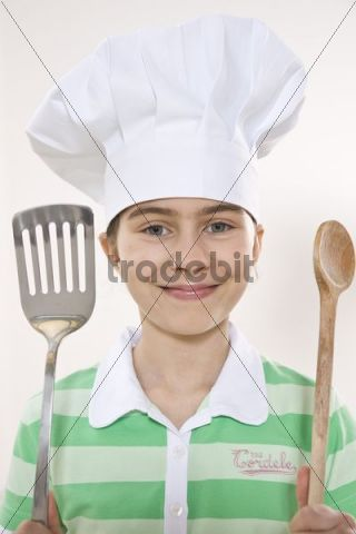 Girl wearing a chef´s hat holding a spatula and a wooden cooking spoon