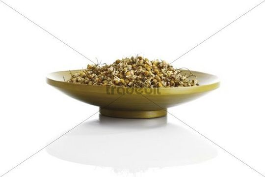 Chamomile flowers in a wooden bowl