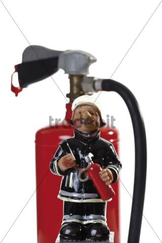 Miniature figure of a fire fighter in front of a fire extinguisher