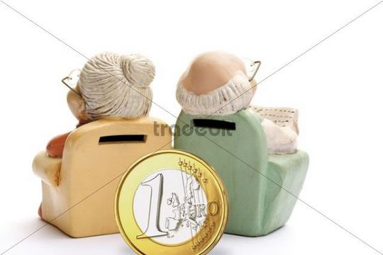Miniature figures of pensioners, grandma and grandpa in an armchair, with euro coin