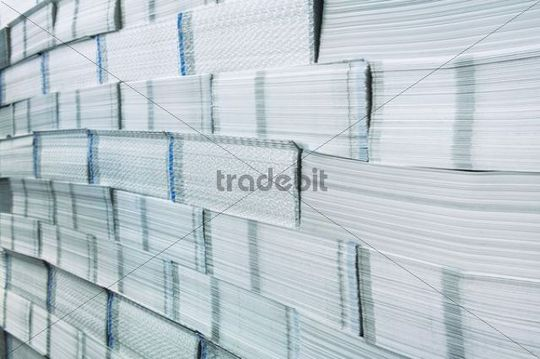 Printing plant, stacked brochures waiting to be processed, detail