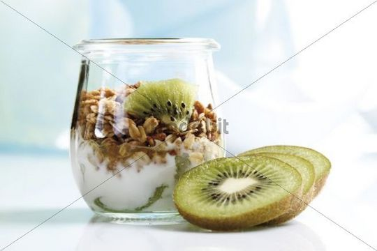 Muesli with yoghurt and kiwi in small glass jars