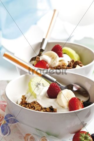 Muesli in two small porcelain bowls with yoghurt, fruit, caramel brittle, raspberries, strawberries, kiwi and a spoon