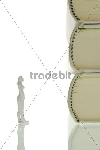 Miniature figure of a woman standing inquisitively in front of a stack of books, symbolic image for knowledge