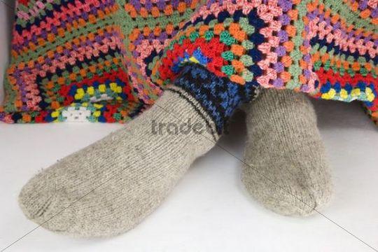 Feet in woollen knitted socks under crocheted blanket