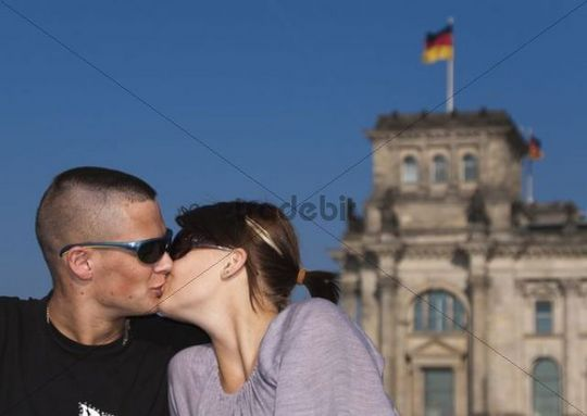 Kissing couple in front of the Reichstag building, Berlin, Germany, Europe