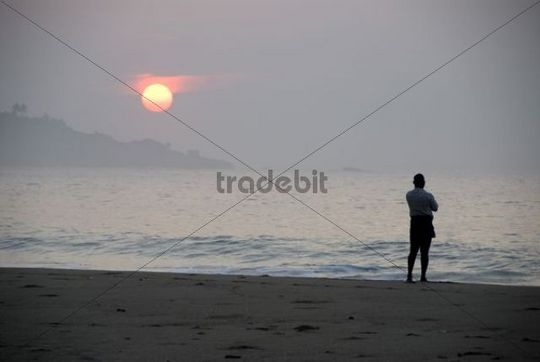 Man standing lonely by the sea, considering the sunrise thoughtfully, Talalla near Dondra, Ceylon, Sri Lanka, South Asia, Asia