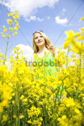Smiling blond girl standing in a field of rape